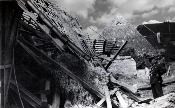 """Oppau 1943/44. Zerstörte Häuser. Ein Wehrmachtsangehöriger auf Heimaturlaub nachdenklich vor den Trümmern des eigenen Heimes. Ob er auch über den Wahnsinn des Krieges nachdenkt? Oder darüber, dass der Ortskern von Oppau zu 37% und der von Edigheim zu 14% zerstört wurde. Oder über die Toten der Angriffe: Während des gesamten Krieges gab es in Oppau 284 Tote, davon 219 in Gemeinschaftslagern untergebrachte Fremdarbeiter/Kriegsgefangene (siehe Buch """"Bomben auf Oppau"""" und """"Oppau-Edigheim 60 Jahre vereint""""), denen die Zuflucht in Bunker und Schutzräume verwehrt wurde."""