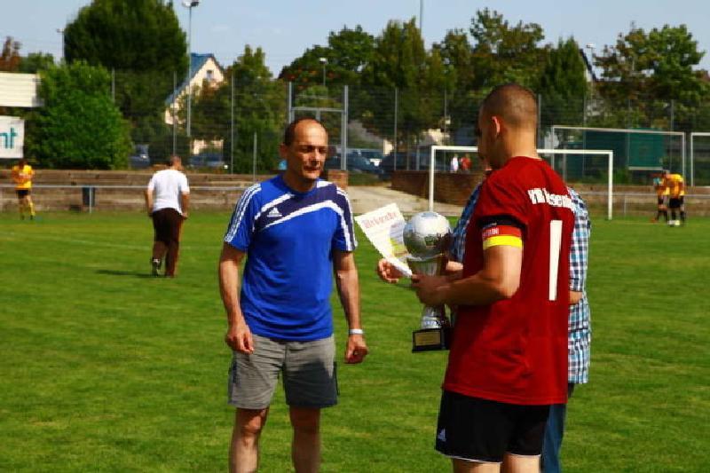 Der 1. Vorsitzende Christian Hettinger überreicht den Pokal an den VfR Friesenheim