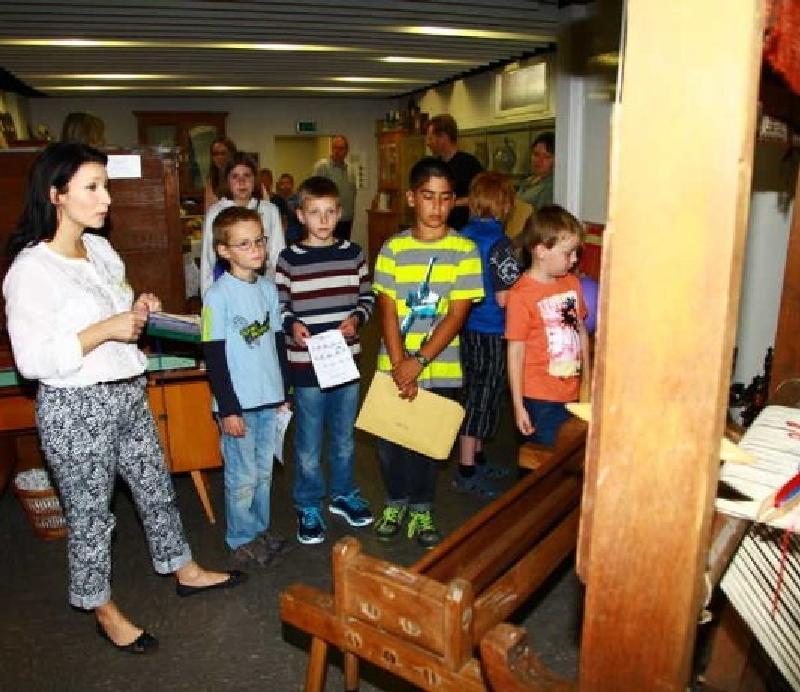 Grundschüler bei Vorführungen an einem alten Webstuhl
