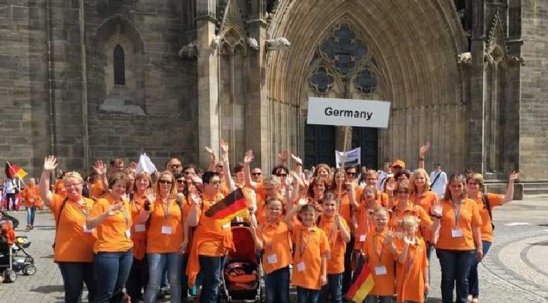 Der JungChor TakeFour während einer Wettstreit-Pause jubelnd vor dem Magdeburger Dom