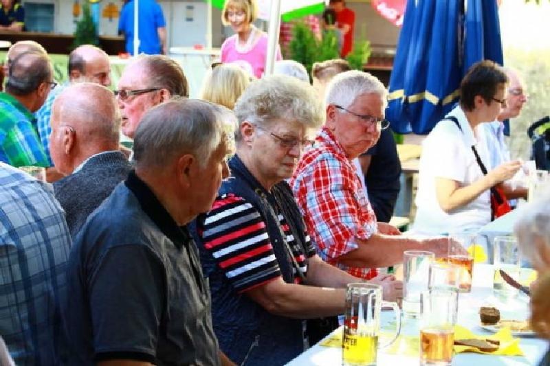 Lassen sich die Speisen und Getränke schmecken: Gäste beim Grillfest