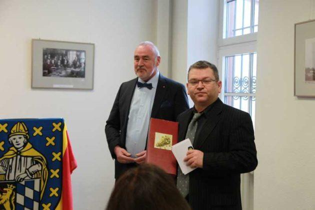 Rolf Schröder übergibt ein Geschenk an Dr. Klaus-Jürgen Becker
