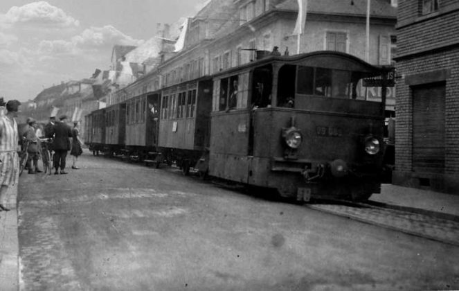 """Am 5.9.1890 hatte die Oppauer Bevölkerung """"das Vergnügen, den ersten Straßenbahnzug in ihren Ort einfahren zu sehen. Das Foto zeigt Dampflok 99 089 mit Wagen in der Friesenheimer-Straße. Es entstand 1920, aber ähnlich dürfte die Situation schon damals gewesen sein. 49.519704, 8.406020"""