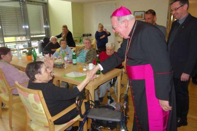 Weihbischof Otto Georgens spricht mit Bewohnern